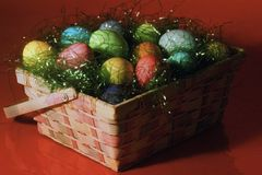 Colored Easter Eggs in Woven Basket. Assortment of colorful hardboiled Easter Eggs nestled in shiny grass peeking out of square woven basket. Suitable as Stock Images