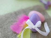 Colored egg with bowknot, colorful feathers on burlap fabric background. Easter holiday greeting concept. Painted egg with bowknot, colorful feathers on burlap stock image