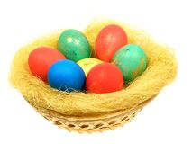 Colored eggs. In a wicker basket from vines within the straw Stock Image