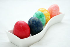 Colored eggs. Five colored eggs in a fancy bowl, white background royalty free stock image