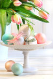 Colored eggs with bows and tulips Stock Photography