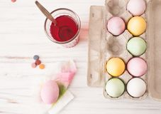 Colored eggs in a box and painted egg with a glass of diluted paint. Classes with children in preparation for Easter. Children`s creativity. Copy space text Stock Photos