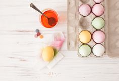 Colored eggs in a box and painted egg with a glass of diluted paint. Classes with children in preparation for Easter. Children`s creativity. Copy space text Stock Photo
