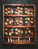 Colored eggs for Easter feast in aged Wooden box on dark rustic background with lettering Happy Easter Stock Photo