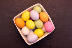 Colored eggs inside bowl on top slate Royalty Free Stock Images