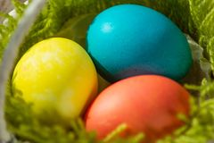 Colored eggs lying in a basket stock images