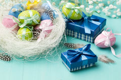 Colored eggs in the nest and presents in blue boxes Royalty Free Stock Images