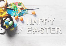 Colored eggs and other decorations on a white wooden table with HAPPY EASTER sign Stock Photos