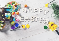 Colored eggs and other decorations on a white wooden table with HAPPY EASTER sign Royalty Free Stock Photo