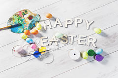 Colored eggs and paint on a white wooden table with HAPPY EASTER sign Stock Photography