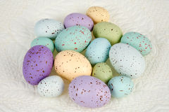 Colored Eggs on Quilted Background. Variety of colored eggs of different sizes, loose against a quilted background.  Room for copy Stock Image