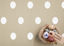 Colored Eggs In A Small Nest. Small nest containing colored eggs over a Easter concept background Royalty Free Stock Images