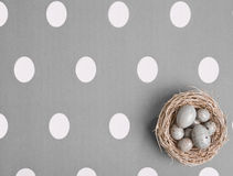Colored Eggs In A Small Nest. Small nest containing colored eggs over a Easter concept background Stock Photo