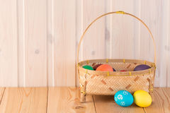 Colored eggs in a straw basket Stock Images