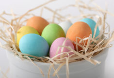 Colored eggs in a straw nest Stock Images