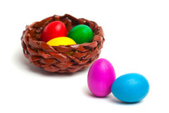 Colored eggs on a white background. Wicker basket with eggs Stock Image