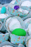 Colored eggs and white powdered cookies in blue paper cups with designs Royalty Free Stock Image