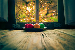 Colored eggs wooden table rural hut Stock Images