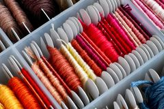 Colored embroidery threads sorting in box. Close-up stock photos