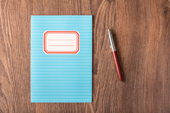Colored exercise book on the wooden table. Colored exercise book on the wooden background Royalty Free Stock Images