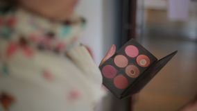 Colored eye shadow palette for cosmetics in hand of make up artist stock video footage