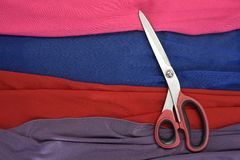 Colored fabrics cut with scissors royalty free stock photography