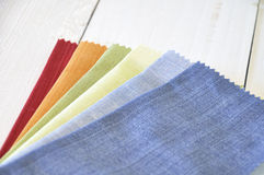 Colored fabrics. Several fabrics with different colors on a white wooden table royalty free stock photos