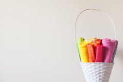 Colored fabrics for sewing lie in a white basket. Colored fabrics for sewing Stock Image