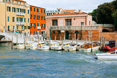 Colored facades of Venice houses and a view of the canal with tourist taxi cabs. Italy, a sunny summer day. Royalty Free Stock Photography