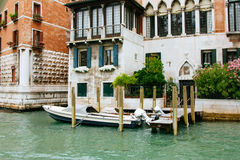 Colored facades of Venice houses and a view of the canal with tourist taxi cabs. Italy, a sunny summer day. Stock Photos