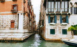 Colored facades of Venice houses and a view of the canal with tourist taxi cabs. Italy, a sunny summer day. Royalty Free Stock Image