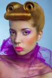 Colored fashion beauty woman with pink tulle and candy colored pearls on her lips and fantasy golden hairstyle on blue background. Stock Image