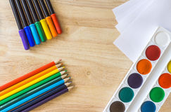 Colored felt-tip pens, lying like rainbow colored pencils, white paper and watercolor on wooden background. Colored felt-tip pens, lying like rainbow colored Stock Image