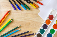 Colored felt-tip pens, pencils, white paper and watercolor on wooden background. Colored felt-tip pens, lying randomly colored pencils, white paper and stock image