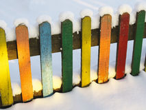 Colored fence. Covered with snow lluminated by the sun stock photo