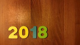 Colored figures  form the number 2018 on wooden background. Stock Photos
