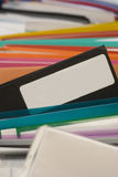 Colored files with space for text. Lots of multi-coloured ring binders and files. Ominous black file pocking out with blank label stock photo