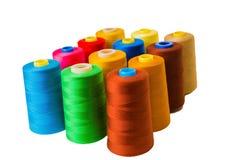 Colored fine thread bobbins. On white Stock Photography