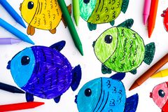 Colored fishes. Child hand drawing with colored crayons. Multicolored fishes. Child hand drawing with colored crayons stock photo
