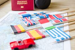 Colored flags on the map of Europe: France, Italy, England UK, Spain, Greece, travel plan. Travelling by car concept. Little red toy car, camera,foreign stock photography