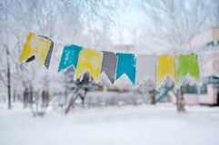 Colored flags on a rope on the street in winter Royalty Free Stock Photos