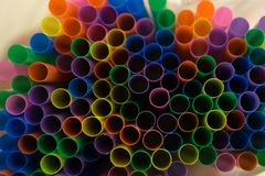 Colored flexible straws in the glass isolated on white background . royalty free stock image