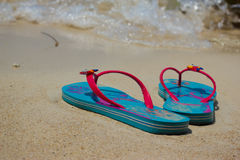 Colored flip-flops on the beach Stock Photography