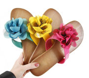 Colored flip-flops with flowers in hand Stock Photography