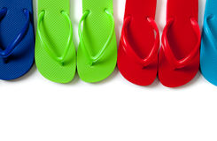 Colored flipflops on a white background. Row of blue, green, red and turguoise flipflops on a white background royalty free stock image