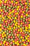 Colored floating extruded fish feed Stock Photography
