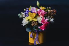 colored bouquet in basket on dark background royalty free stock image