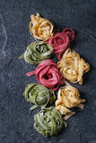 Colored fresh homemade pasta tagliatelle. Variety of colored fresh raw uncooked homemade pasta tagliatelle green spinach, pink beetroot and traditional yellow Royalty Free Stock Photography