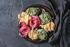 Colored fresh homemade pasta tagliatelle. Variety of colored fresh raw uncooked homemade pasta tagliatelle green spinach, pink beetroot and yellow on wooden Stock Photo