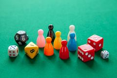 Colored game figures chips for board games. Collection of dice cubes on green table stock photos